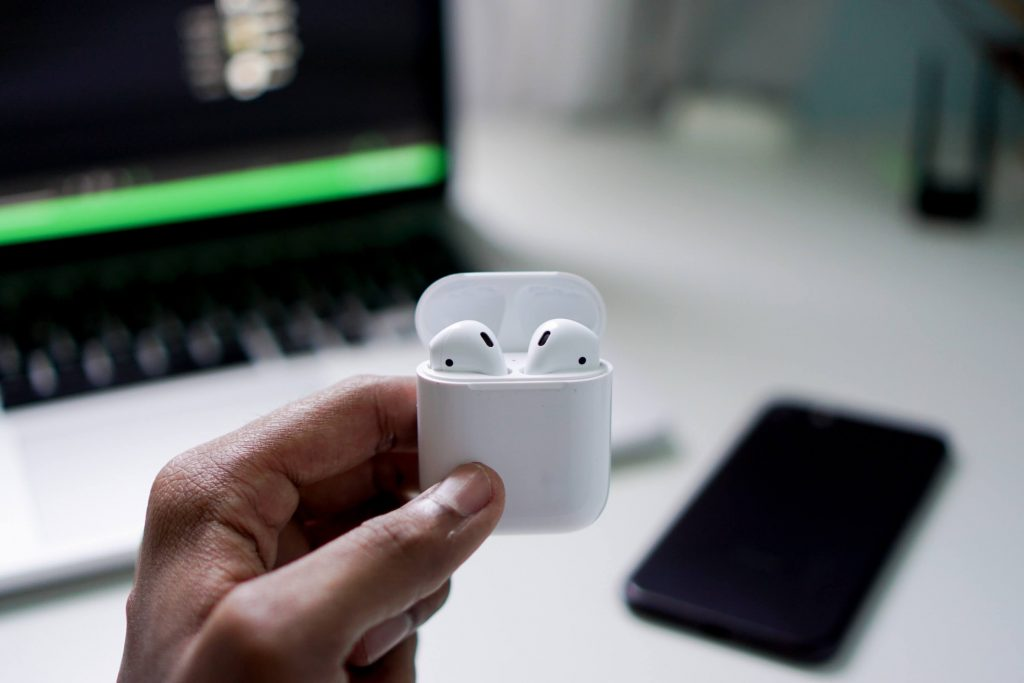 A person holding Apple AirPods case in hands