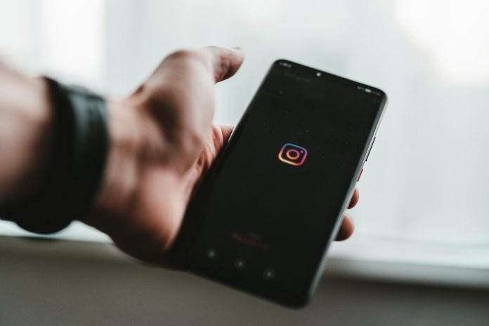 A person holding a phone showing Instagram logo
